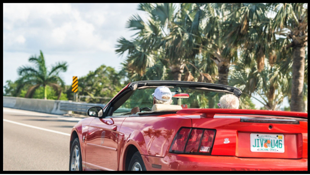 Elderly couple driving down the street in a convertible in Florida.