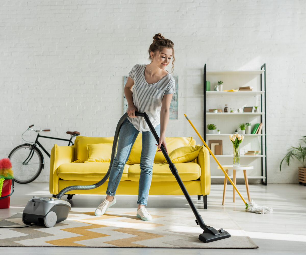 girl cleaning carpet with vaccum cleaner
